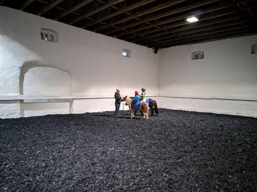Kinder auf Ponies in der Reithalle